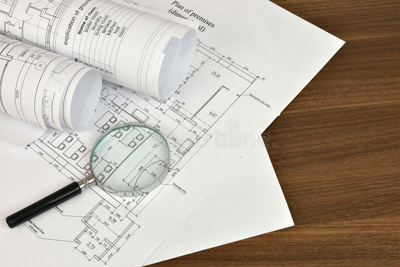 Construction drawings and magnifying glass. On a wooden surface. Workplace architect stock images