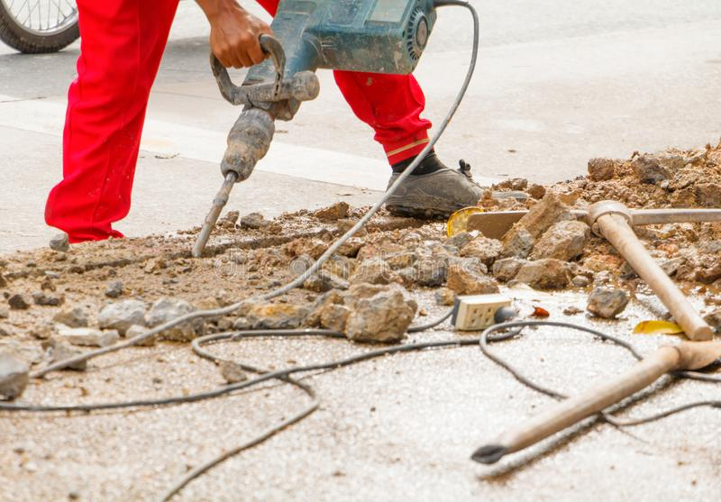 Construction drilling repair worker on road surface with heavy duty machine drill motion.  stock photos