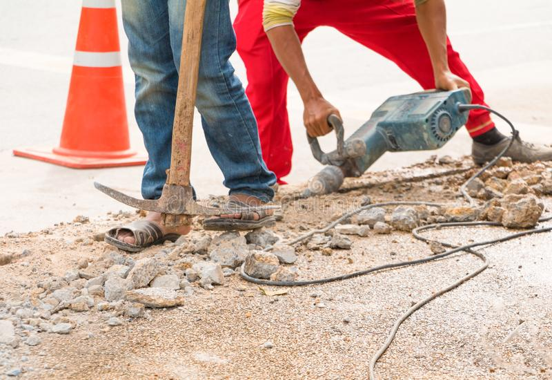 Construction drilling repair worker on road surface with heavy duty machine drill motion.  stock images