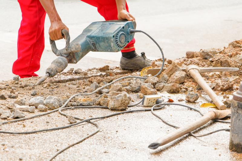 Construction drilling repair worker on road surface with heavy duty machine drill motion.  royalty free stock images