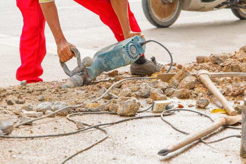 Construction drilling repair worker on road surface with heavy duty machine drill motion.  stock photography