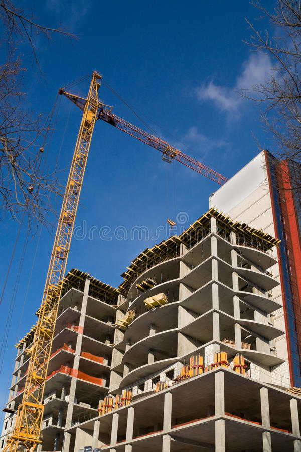 Construction of dwelling house. Crane working on the construction of residential house royalty free stock photo