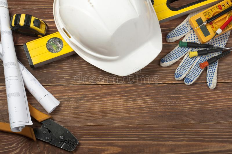 Construction and electrical tools,drawings and white helmet on wooden background . Copy space for text. royalty free stock photos