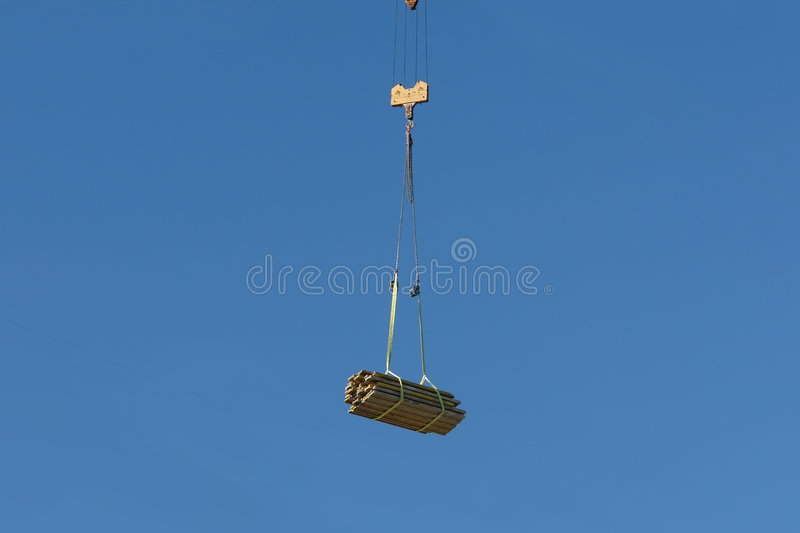 Construction elements. Being transported by jib crane over blue sky royalty free stock image