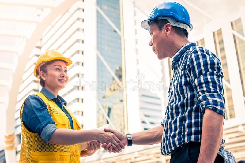 Construction and engineer concept. Construction worker in protective uniform shaking hands meeting for architectural project. Working with partner. Worker and royalty free stock photography