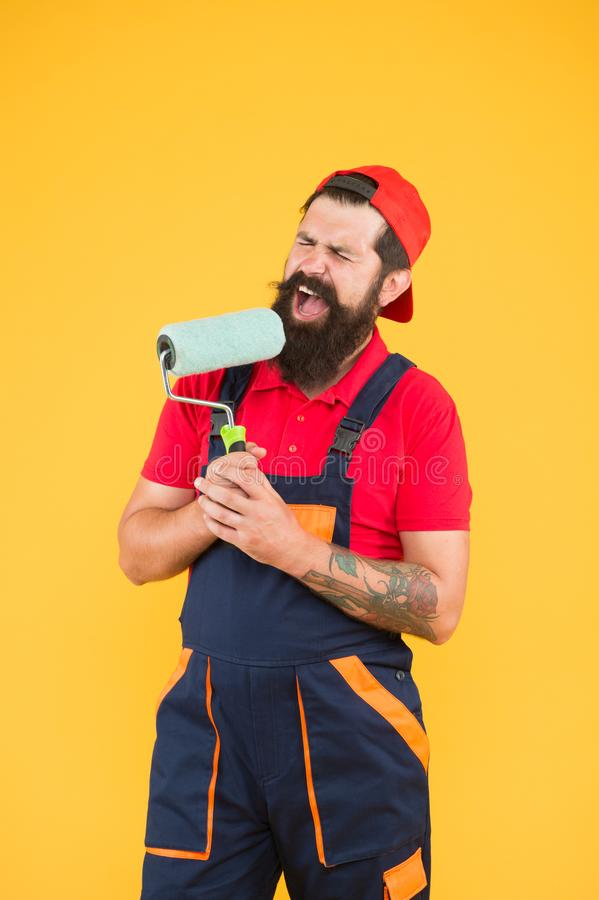 Construction. engineer designer ready to paint wall. repair concept. bearded man worker sing in painting roller. hipster royalty free stock image