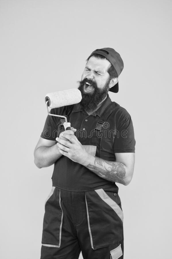 Construction. engineer designer ready to paint wall. repair concept. bearded man worker sing in painting roller. hipster royalty free stock images