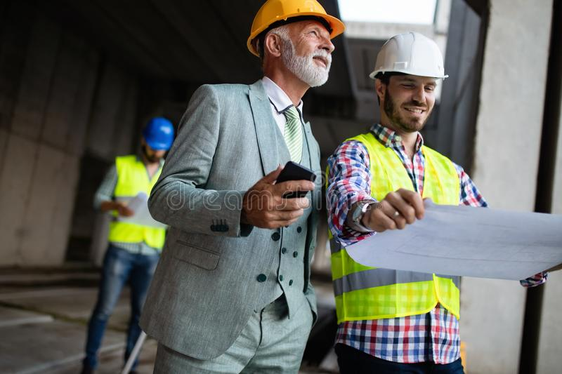 Construction engineer with foreman worker checking construction site. Construction engineer architect with foreman worker checking construction site royalty free stock images