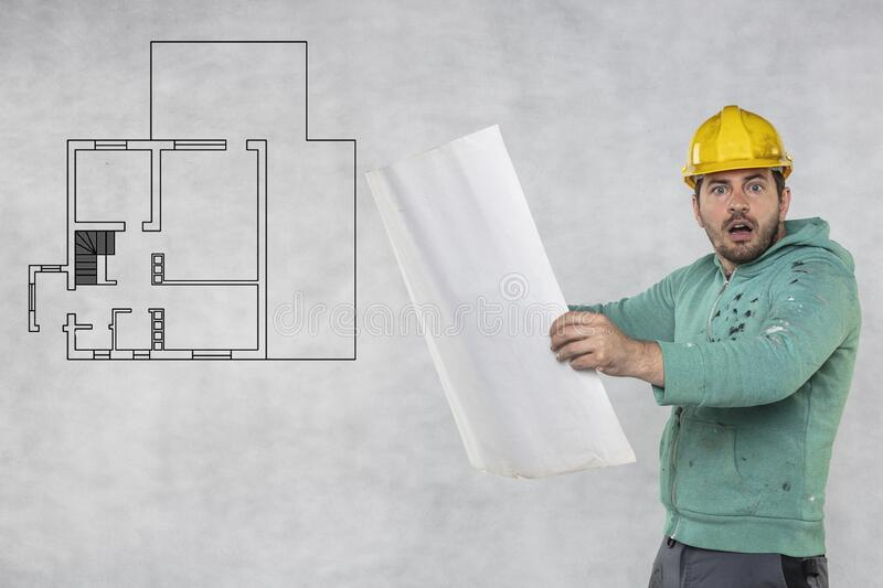 The construction engineer is looking at the apartment plans royalty free stock images