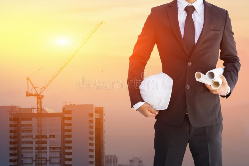 Construction engineer in safety suit trust in team holding white safety hard hat security equipment on construction site royalty free stock photos
