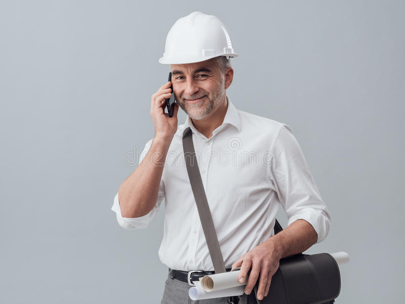 Construction engineer using a smartphone. He is having a phone call royalty free stock photo