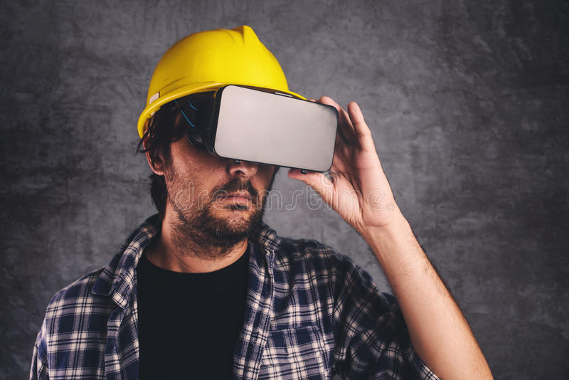 Construction engineer with VR goggles managing building project stock image