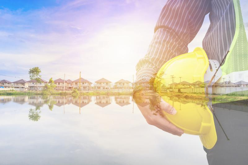 Construction engineer worker hold helmet double exposure with residential new house in progress royalty free stock photo