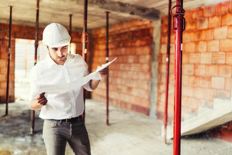Construction engineer working on house building site - reading paper plans and coordinating workers. Construction industry engineer working on house building stock image