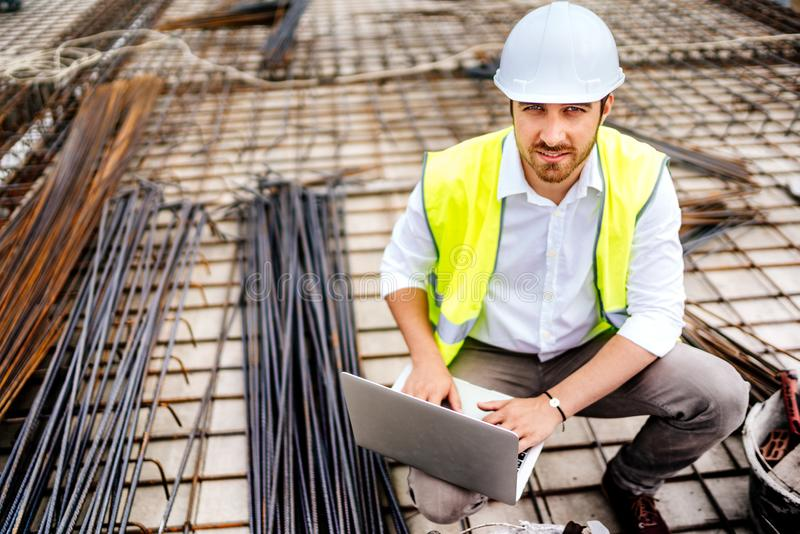 construction engineer working on laptop, wearing safety equipement and coordinating workers royalty free stock photography