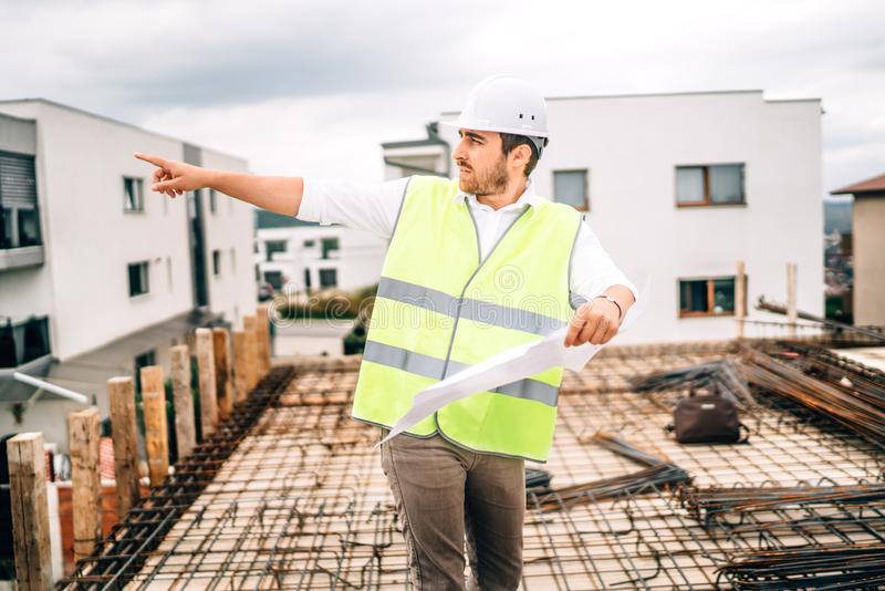 construction engineer working on construction site, pointing and directing workers royalty free stock photos