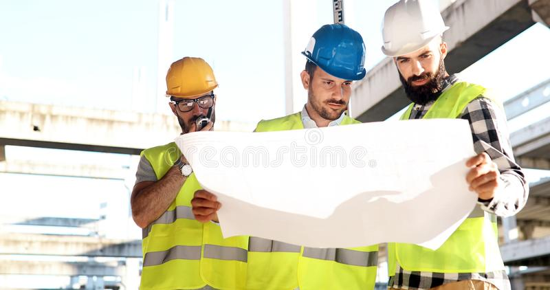 Construction engineers discussion with architects at construction site. Construction engineers discussion with architects at building site royalty free stock photography