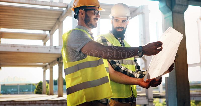 Construction engineers discussion with architects at construction site. Construction engineers discussion with architects at building site stock photo