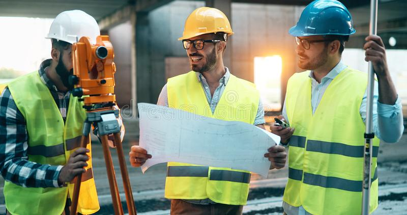 Construction engineers discussion with architects at construction site. Construction engineers discussion with architects at building site royalty free stock photo