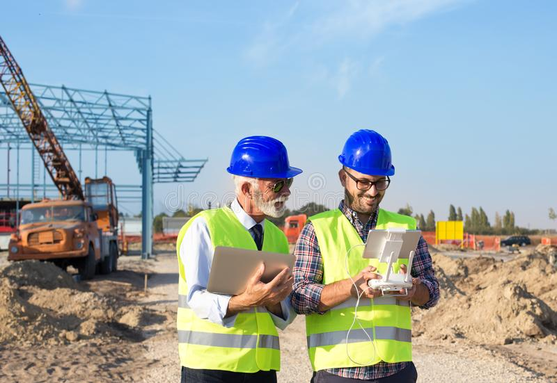 Construction engineers with drone at building site royalty free stock image