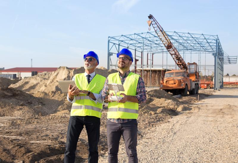 Construction engineers with drone at building site stock image
