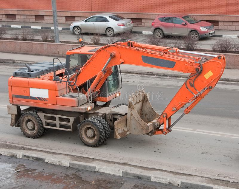 Orange excavator rides on paved road in city limits. Construction equipment in motion on the street stock photos