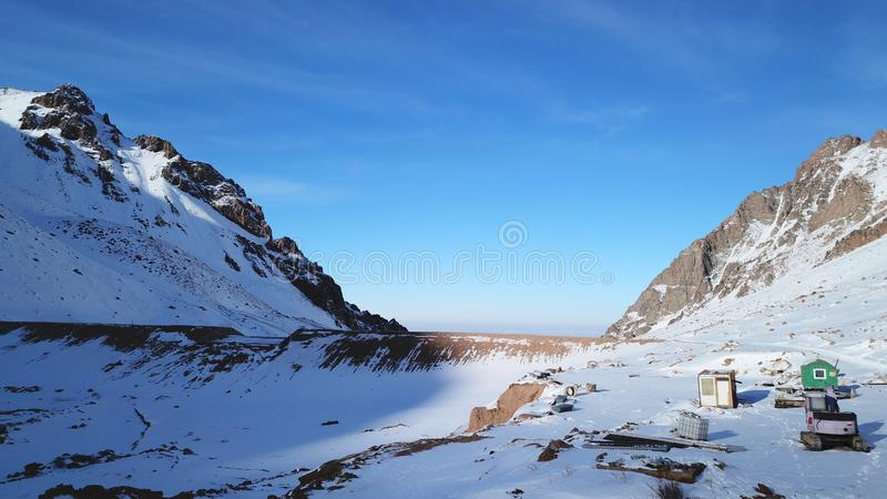 Construction equipment in the snowy mountains. Small house, tractor, equipment for snow the dam. Among mountains and rocks. View of the blue sky and white stock images
