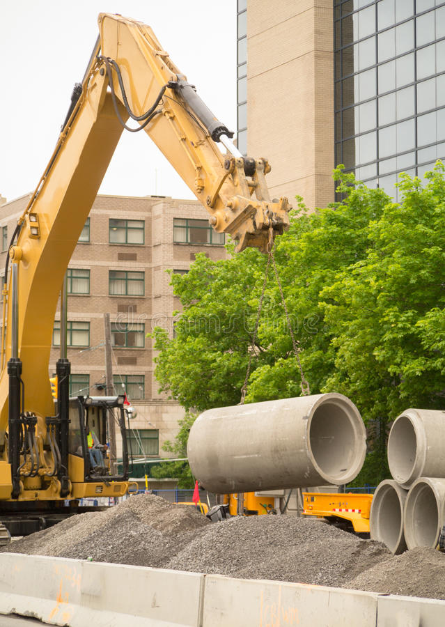 Construction excavator lifting concrete pipes stock image