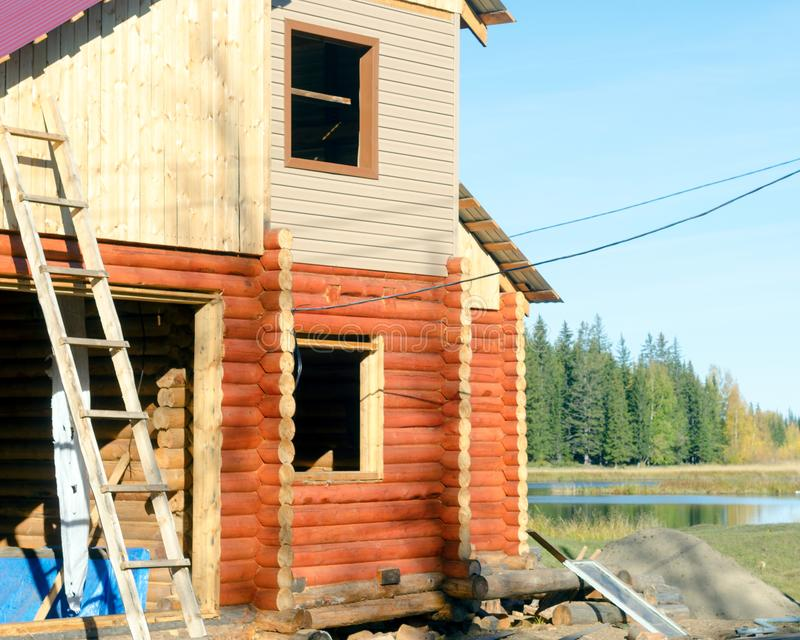 Construction of the facade of a new house made of pine timber with stairs leaning against the walls and Windows. royalty free stock image