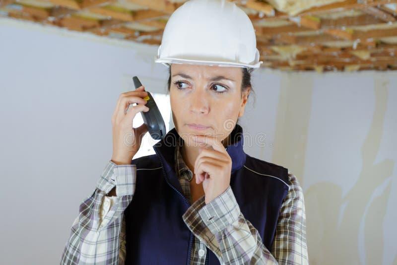 Construction femelle utilisant le talkie-walkie dans le site photo libre de droits