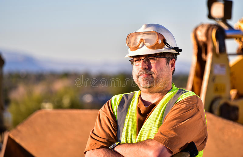 Construction Foreman with Folded Arms. Displeased foreman on a construction site with arms folded stock images