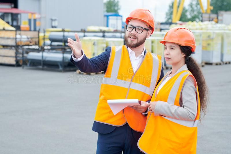 Construction Foreman Giving Instructions to Worker. Waist up portrait of successful bearded businessman wearing hardhat and holding clipboard talking to female stock images