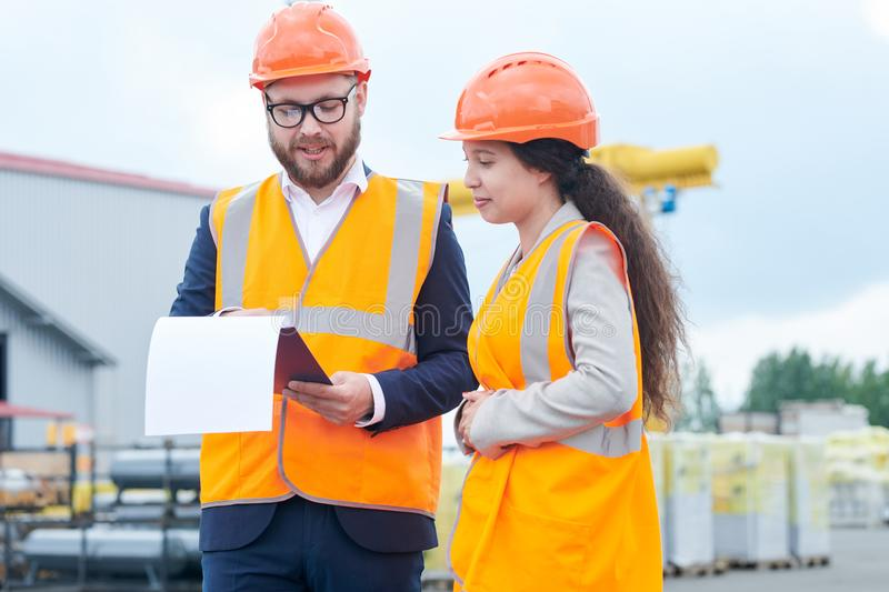 Construction Foreman Instructing Worker. Waist up portrait of successful bearded businessman wearing hardhat and holding clipboard talking to female factory stock photo