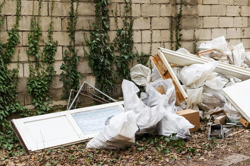 Construction garbage after apartment repair. Pile of construction waste near a white brick wall. Construction debris in white bags stock photography