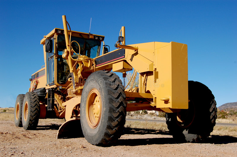 Construction grader on dirt road. Yellow heavy construction equipmement used for road grading stock photos