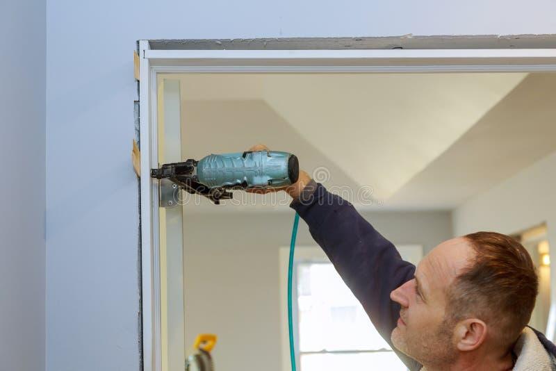 Construction handyman using air nail gun installing the interior door of apartment stock photos