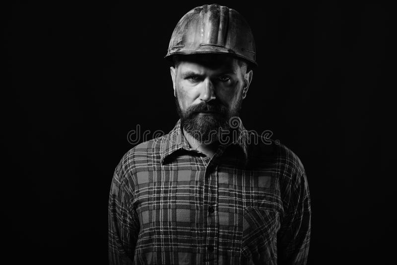Construction and hard work concept. Builder or repairer with thick beard. Man with serious face. Expression isolated on black background. Worker with brutal stock photos