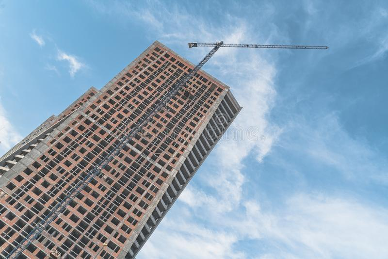 Construction activity of high-rise buildings in the city with turret slewing crane in daytime. Construction of high-rise buildings with turret slewing crane in royalty free stock photos