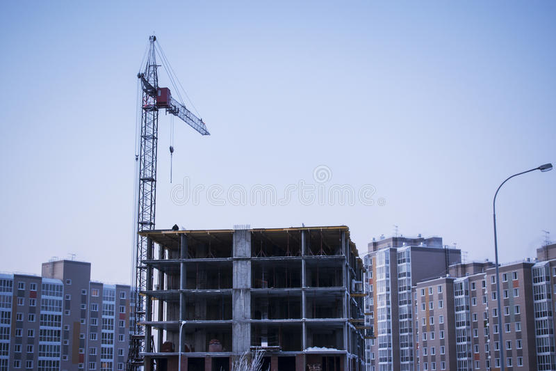 The construction of high-rise residential building. And a crane royalty free stock photography
