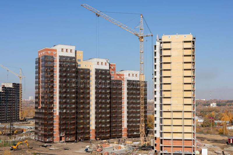 Construction of high-rise residential building. cranes working on building complex, with clear blue sky royalty free stock photos