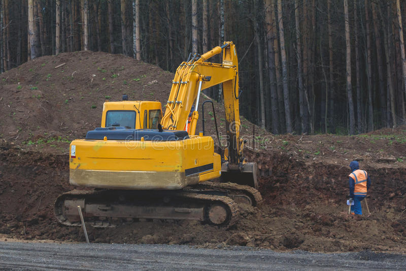 Construction of the highway - yellow excavator at work royalty free stock photography