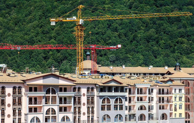 Construction of hotels in Sochi mountain ski resort for the Olympics 2014. Lifting cranes tower above the buildings on green fores. Sochi, Russia - August 12 stock photos