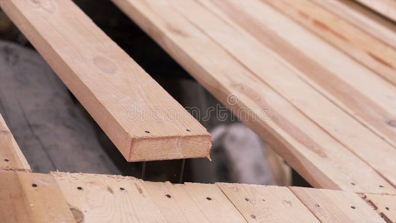 Construction of a house made of timber. Clip. Close up of wooden board on the roof of unfinished ecological house royalty free stock image
