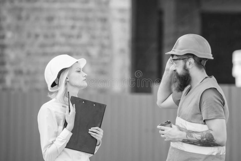 Construction industry concept. Relationships construction client and participant building industry. Discuss progress. Plan. Woman engineer and bearded brutal royalty free stock images