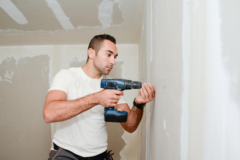 Construction industry worker with tools and drill renovating house in construction site royalty free stock photography