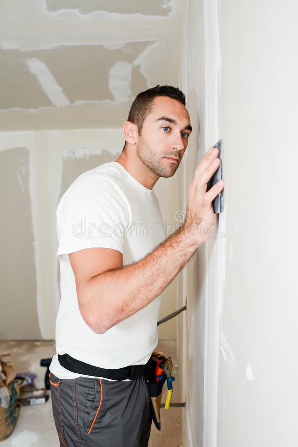 Construction industry worker with tools plastering walls and renovating house in construction site royalty free stock photos