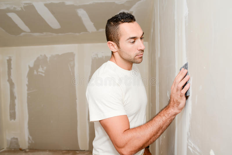 Construction industry worker with tools plastering walls and renovating house in construction site royalty free stock photo