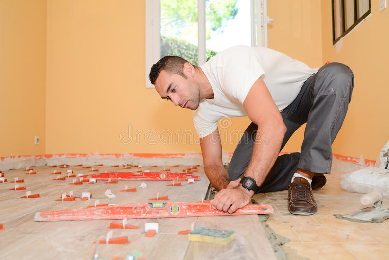 Construction industry worker with tools renovating house with floor tiles in construction site royalty free stock photos