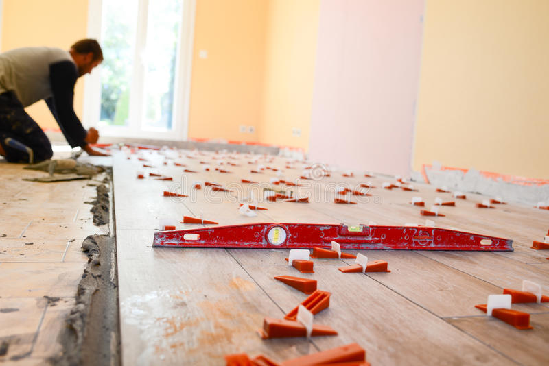 Construction industry worker with tools renovating house with floor tiles in a construction site royalty free stock photography