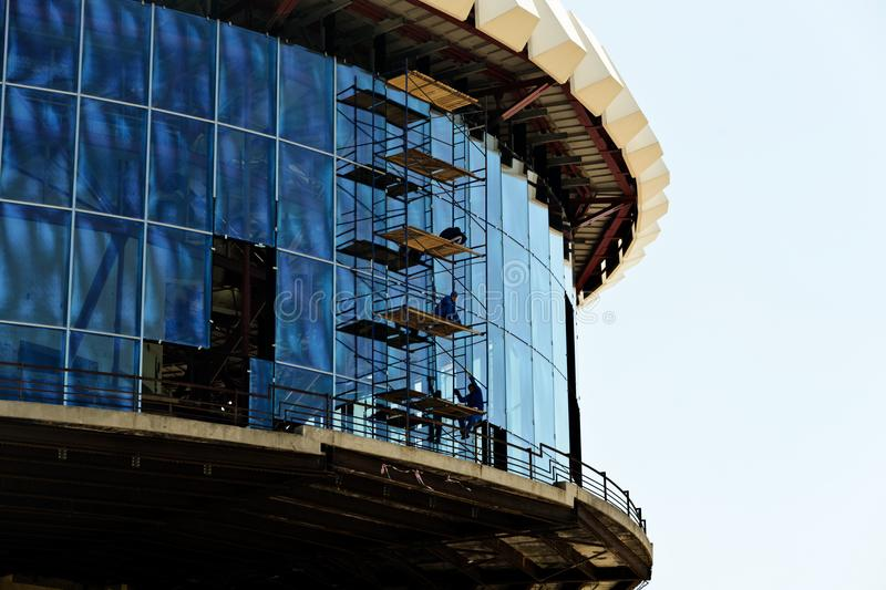 Construction and installation work at height. A pair of installation workers fix the double-glazed Windows at a height, working on specially constructed stock photography